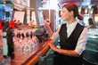 Happy barmaid using touchscreen till - 76039989