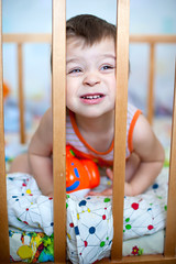 Baby boy playing in the crib