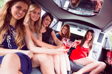 Happy friends drinking cocktails in limousine