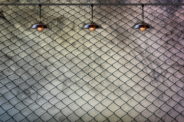 Lamp with wired fence and Grungy concrete wall