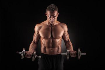 Muscular man with dumbbells on black background © bondarchik