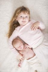 Große Schwester mit Baby von oben