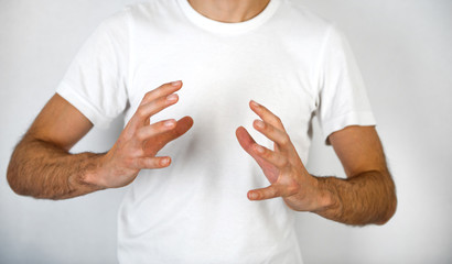 Man making a hand gesture to clasp a round object