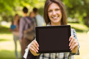 Smiling student with a shoulder bag and showing screen at tablet