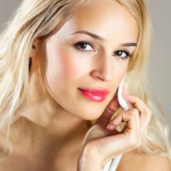 Beautiful young woman applying creme