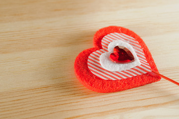 The heart of felt on wooden background