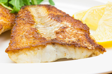 White fish with lemon on white plate