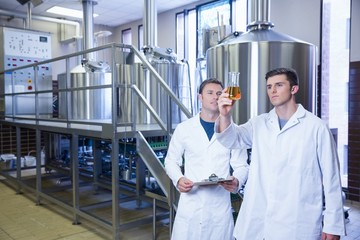 Two men in lab coat looking at the beaker with beer