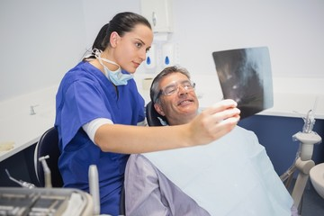 Smiling dentist showing x-ray to her patient