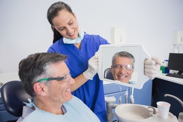 Smiling dentist showing teeth of her patient with a mirror