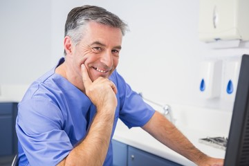 Portrait of a smiling dentist using computer