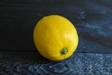 One lemon on the black background