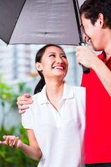 Asian couple walking with umbrella through rain