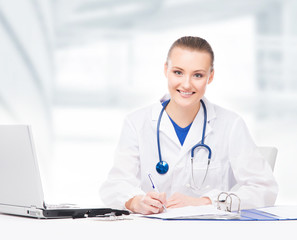 Young, professional and cheerful female doctor working in office