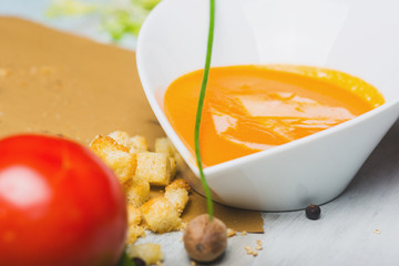 Tomato soup with croutons and shredded cheese on the wooden