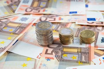 Pila di monete su banconote euro
