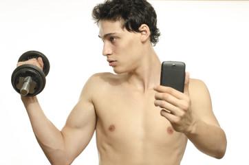 Skinny man taking selfie with phone while training biceps