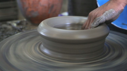 Close up of hands working clay on potter's wheel