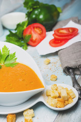 Bowl of gazpacho with  tomato and other vegetables on wooden