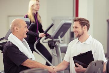 trainer im fitness-center schüttelt senior die hand