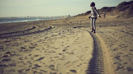 Teen girl walking on the beach. Handheld shot