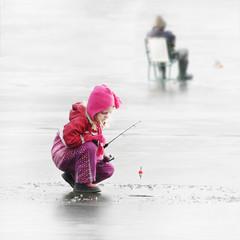 Little child fishing on a frozen lake in winter.