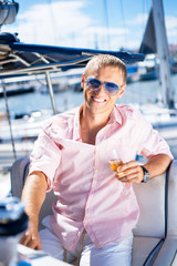 Young and handsome blond man on a sailing boat