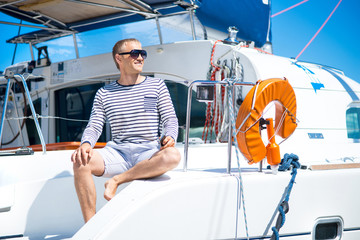 Young and handsome man on a sailing boat
