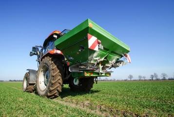 Ackerbau, Traktor mit Düngerstreuer bei der Frühjahrsdüngung