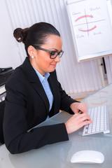 frau arbeitet im büro am computer