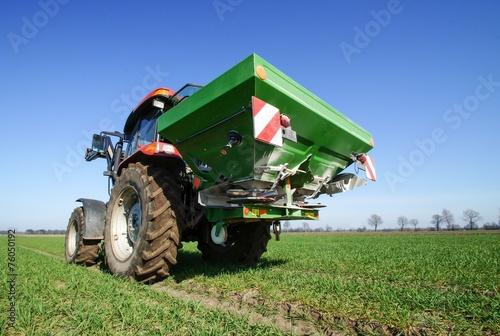 Leinwanddruck Bild Ackerbau, Traktor mit Düngerstreuer bei der Frühjahrsdüngung