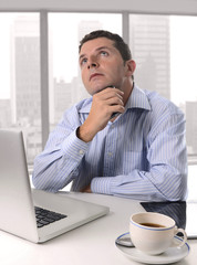 businessman in office thinking with computer and coffee