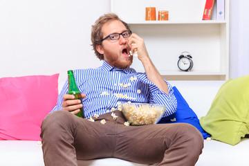 Man eating popcorn on the sofa