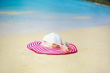 sunhat on the beach sand behind blue ocean