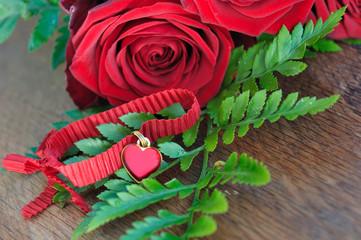 cœur en pendentif parmi fougères et roses