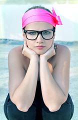 Funky woman wearing a pink headband and geek glasses.