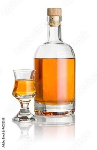 Flasche und Schnapsglas mit bernsteinfarbener Flüssigkeit - 76052313