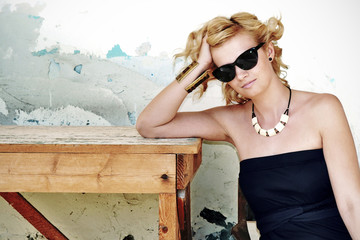 Blonde woman wearing sunglasses sitting by the table.