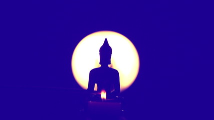Buddha statue with candle and moving incense stick