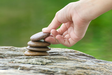 Hand put stone building a pile of zen stones