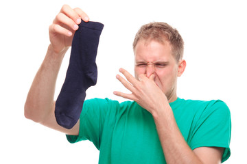 Man holding smelly socks and clogged nose