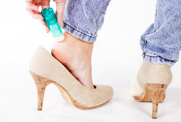 Woman in high heels using cosmetics for foot