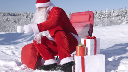 Santa Claus relaxing in lounge chair at winter ski resort