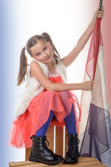 a pretty little girl sitting on a box with a french flag