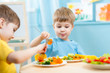 children eating in kindergarten - 76055984