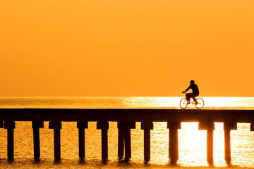 silhouette people driving bicycle  on wood bridge with sunset