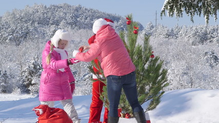 Family decorating a Christmas tree in winter forest