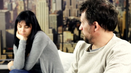 Couple at home sitting on sofa having problems talking