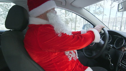 Santa Claus driver driving car through the snow in winter forest