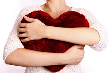 woman hugging heart-shaped pillow